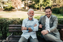 Portrait Of A Business Family Outdoors. Two Men Sitting In The Park Looking At Camera.