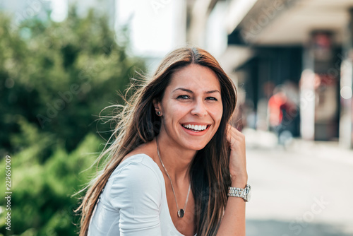 Fototapeta Portrait of gorgeous smiling young woman outdoors.