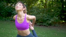 Pretty Woman Talking And Laughing While Doing Yoga Outside. Smiling Girl Stretches In Half Frog Pose And Relaxes. Fitness And Exercise Outdoors.