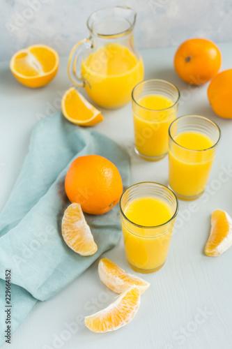 Fotobehang Stof Glasses of freshly squeezed orange juice and oranges