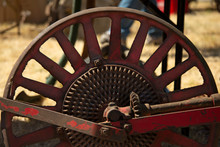 Eye Level Perspective Of Vintage Seed Planter Wheel With Neutral Out Of Focus In Background