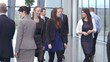 Diverse group of business people walking through a light modern office space