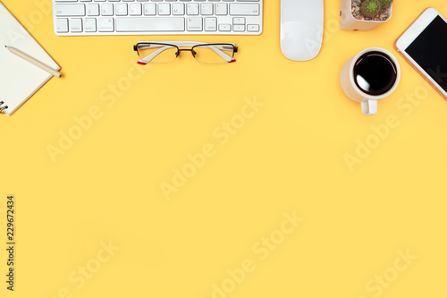 Fototapety, obrazy: workspace business desk with computer, coffee cup, notebook and glasses on yellow pastel background