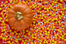Big Pile Of Halloween Candy Corn On An Orange Background, With A Ceramic Orange Pumpkin