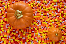Big Pile Of Halloween Candy Corn On An Orange Background, With Two Ceramic Orange Pumpkins