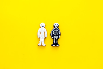 Halloween traditions. Halloween gingerbread in shape of evil characters on yellow background top view space for text