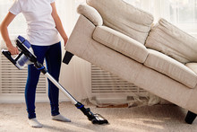 Portrait Of Young Woman In White Shirt And Jeans Cleaning Carpet Under Sofa With Vacuum Cleaner In Living Room, Copy Space. Housework, Cleanig And Chores Concept