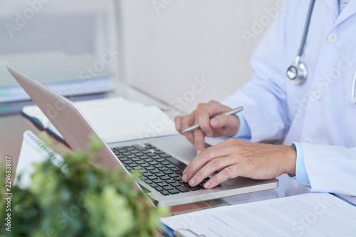Fotografia  Cropped image of general practitioner working on laptop at her table