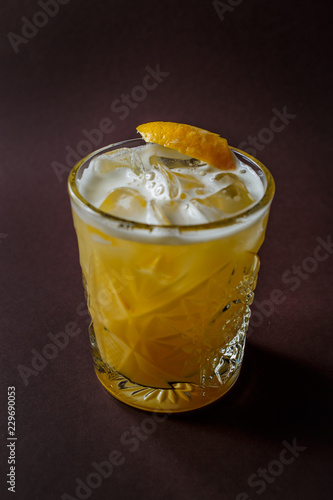 Glass of yellow alcohol cocktail with ice and slice of lemon on elegant dark brown background