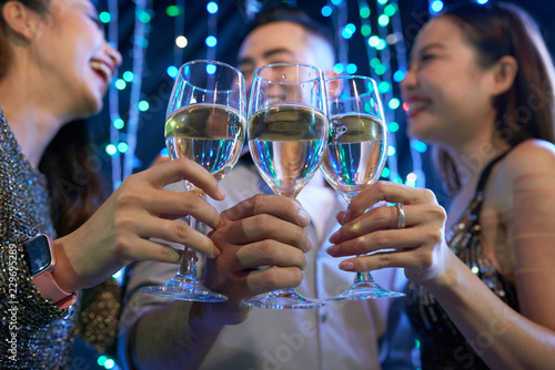Young people clinking glasses of champagne at night party