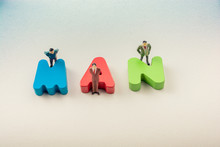 Tiny Figurine Of Men Beside Wooden Letters Say MAN