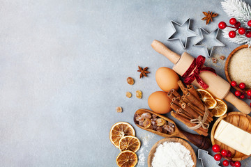Fototapeta Bakery background with ingredients for cooking christmas baking decorated with fir tree. Flour, brown sugar, eggs and spices on kitchen table top view.