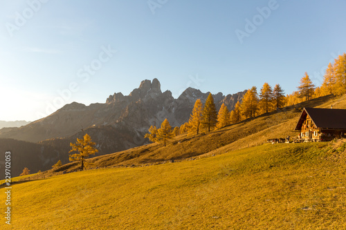 Autumn in Austrian Alps. Mountain landscape with fall colored larch trees and little alpine hut at sunset