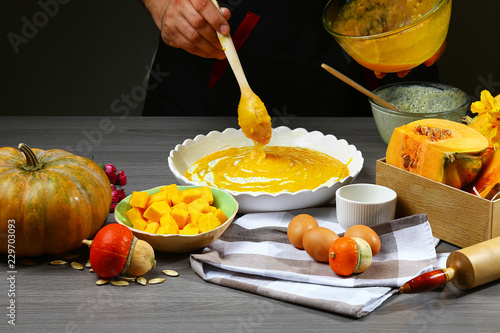 Photo  Traditional pumpkin pie preparation with cheese, pumpkin and ingredients on rust
