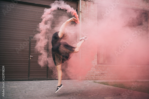 attractive young woman dancing in pink smoke on street