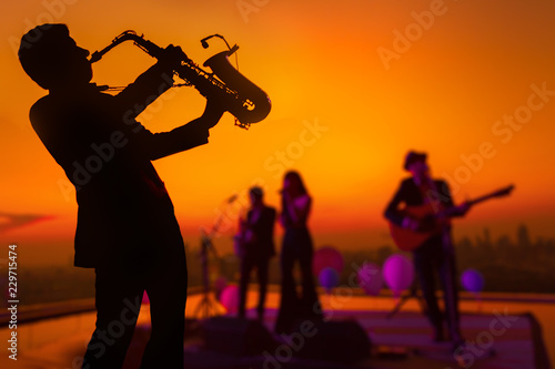 Photo  Silhouette saxophone musician man showing with blurry jazz trio band and twilight cityscape background