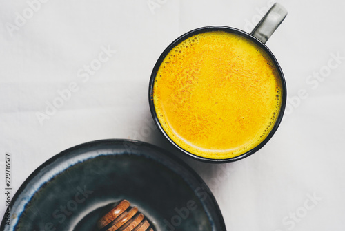 Fototapeta Golden milk with turmeric powder in cup over white background, flat lay top view
