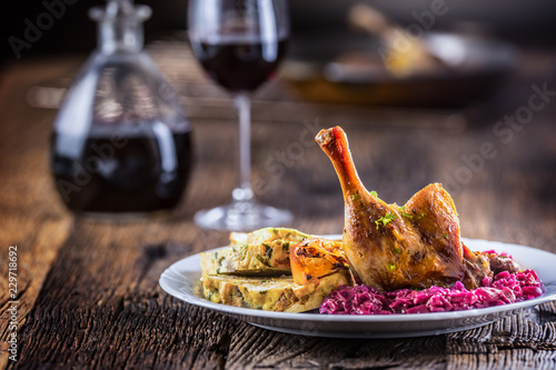 Fototapeta Portion of roast duck leg red cabbage homemade dumplings on plate and red wine on the background obraz