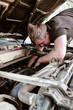 The bright man repairs the car. Hands in oil. Engine repair and fuel system. Masters works. Outdoor hood machine.Mechanic