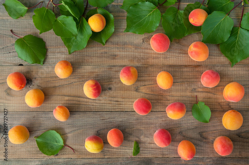 Ripe tasty fruit of apricot tree with leaves on a wooden table viewed from above Tapéta, Fotótapéta