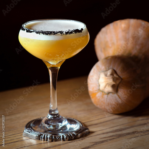 pumpkin alcohol cocktail in a glass and pumpkin on the table
