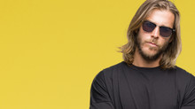 Young Handsome Man With Long Hair Wearing Sunglasses Over Isolated Background Skeptic And Nervous, Disapproving Expression On Face With Crossed Arms. Negative Person.