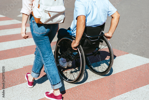 Billede på lærred cropped image of disabled boyfriend in wheelchair and girlfriend crossing crossw