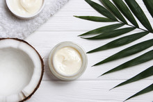 Tropical Leaf, Care Cosmetics And Coconut On A Wooden Table. Top View. Means For Hair, Body, Skin. Flatlay