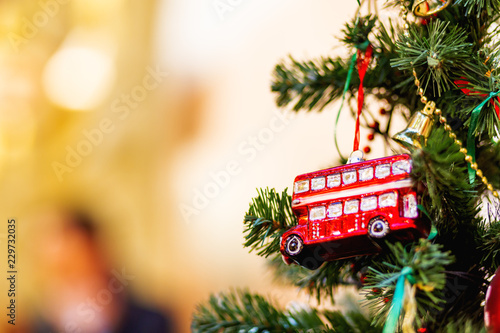 Fotografia Fir tree decorated with toy double decker bus and light bulbs for Christmas and New Year celebration