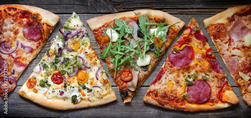 Photo Pieces of pizza of different various types on old retro boards banner concept