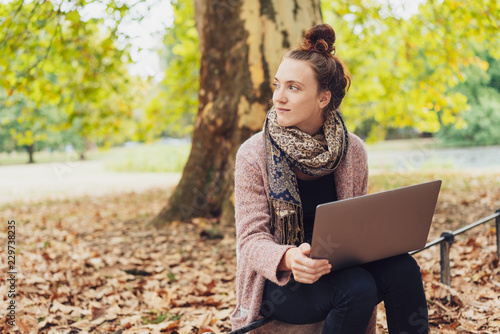 Photo  Young woman studying in an autumn park