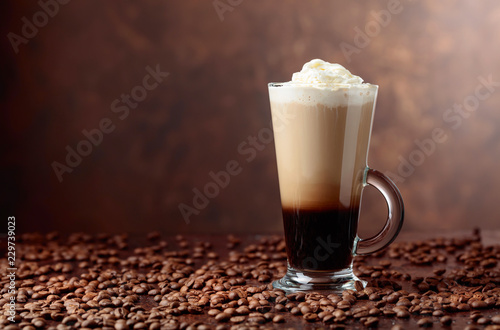 Coffee drink or cocktail with cream on a brown background.