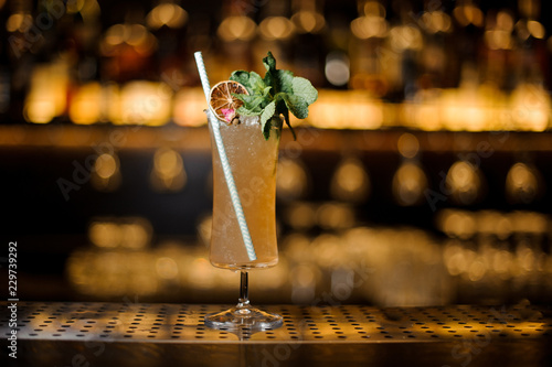 Elegant cocktail glass filled with tasty Sherry Cobbler drink decorated with mint, straw and orange slice
