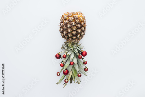 Fotografie, Obraz  top view of red christmas balls on fresh pineapple isolated on white