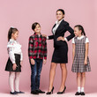 Cute smiling happy stylish children and female teacher on pink background. Beautiful stylish teen girls and boy standing together and posing at studio. Classic style. Kids fashion and emotions concept