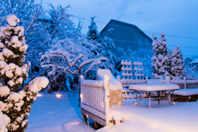 Garden And Patio After Snowfall At Night.