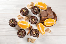 Delicious Chocolate Cupcakes With Orange On Wooden Table