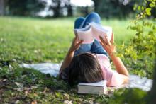 Woman Reading A Book In The Garden.