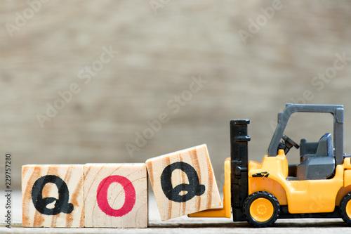 Fotografía  Toy forklift hold letter block  in word qoq (abbreviation of quarter on quarter)
