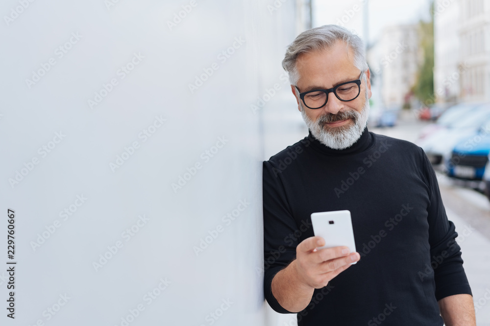 Fototapeta Smiling relaxed man reading a mobile message