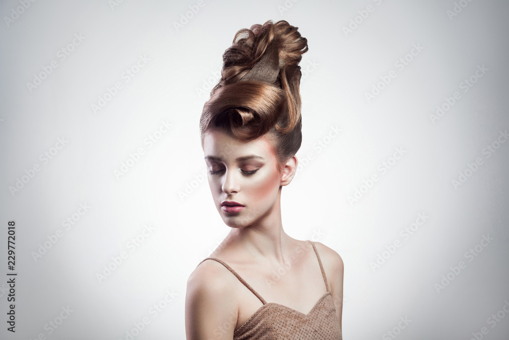 Fototapeta portrait of attractive brunette woman with stylish hairdo and makeup posing with closed eyes on isolated grey background. indoor, studio shot on copy space.