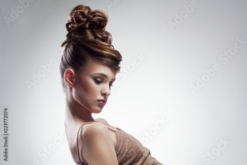 Door stickers Hair Salon side view of attractive brunette woman with stylish hairdo and makeup posing on isolated grey background. indoor, studio shot on copy space.