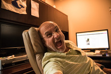 Old Bald Man Baby Boomer Making Funny Face While Reclining In Leather Executive Chair At Desk With His Computer Monitor In Background