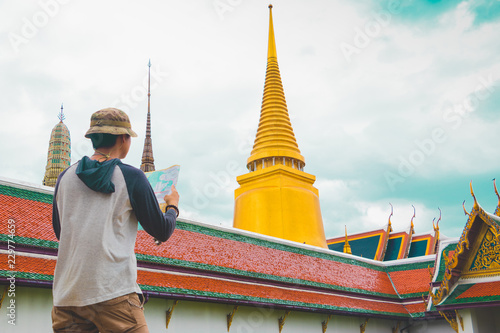 Back side of young Asian male tourist searching direction on map in Wat Phra Kaew, Bangkok, Thailand on holidays.