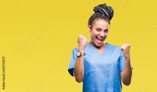 Young braided hair african american girl professional nurse over isolated background very happy and excited doing winner gesture with arms raised, smiling and screaming for success