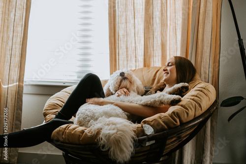 Valokuvatapetti Girl holding her dog on comfy chair