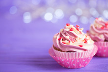Closeup Two Cupcakes With Creamy Pink And White Top Decorated With Little Hearts On Purple Bokeh Background.