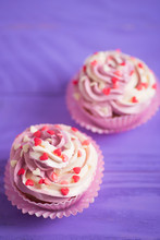 Closeup Two Cupcakes With Creamy Pink And White Top Decorated With Little Hearts On Purple Wooden Background