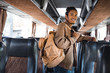 smiling multiracial male tourist with backpack looking at camera in travel bus