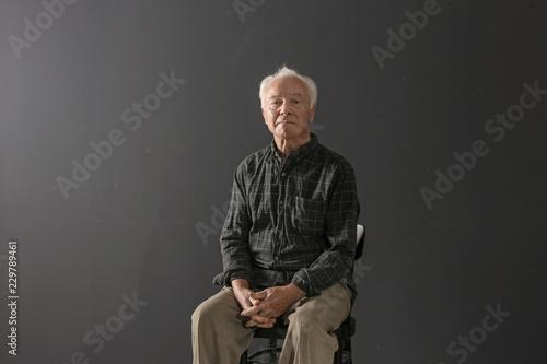 Valokuva  Portrait of poor elderly man sitting on chair against dark background
